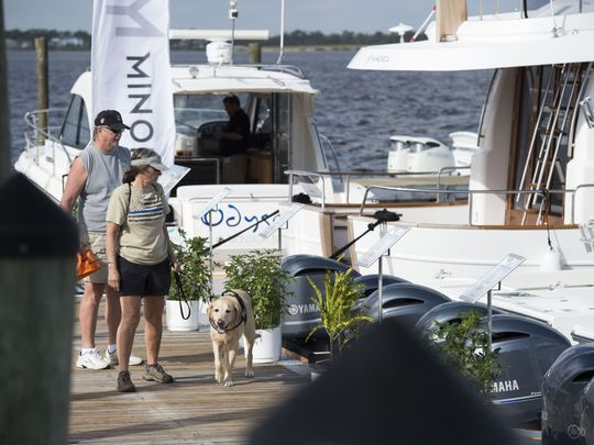 Cliff Abrams (from left), L.A. Abrams and Darel the dog browse the selection at the 44th annual Stuart Boat Show on Friday, Jan. 12, 2018 along Old Dixie Highway in Stuart. The show features over 200 exhibitors selling boats, accessories, clothing, jewelry, fishing gear and more. The show continues 10 a.m. to 6 p.m. Saturday and 10 a.m. to 5 p.m. Sunday. For more information, go to stuartboatshow.com. (Photo: LEAH VOSS/TCPALM)